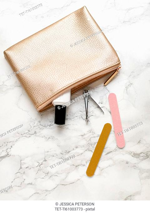 Manicure accessories and purse on marble background