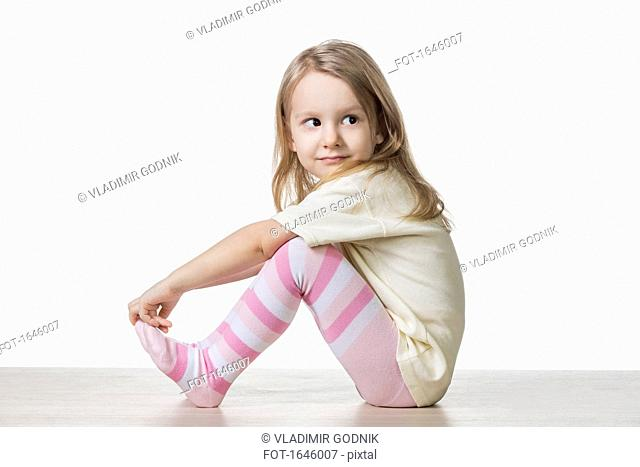 Side view of cute girl sitting on floor against white background