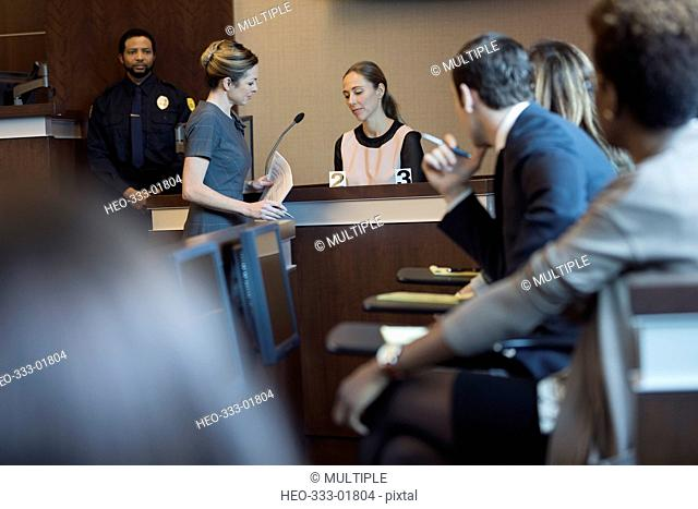 Female attorney with evidence interrogating witness on the stand in legal trial courtroom