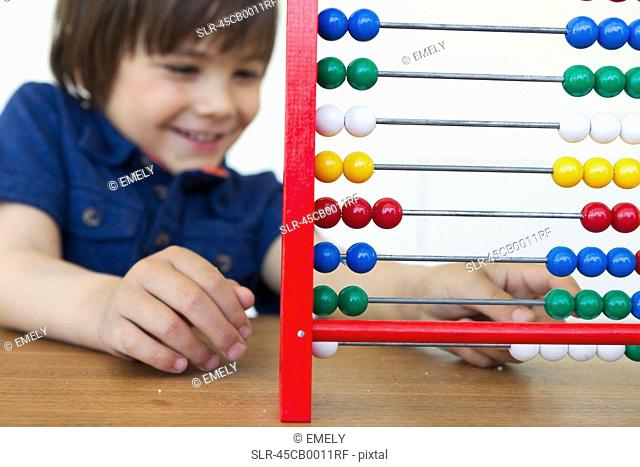 Smiling boy playing with abacus