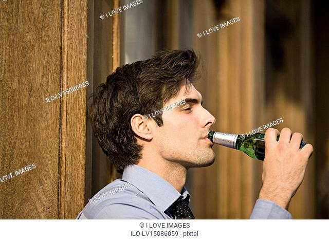 A businessman drinking a bottle of beer