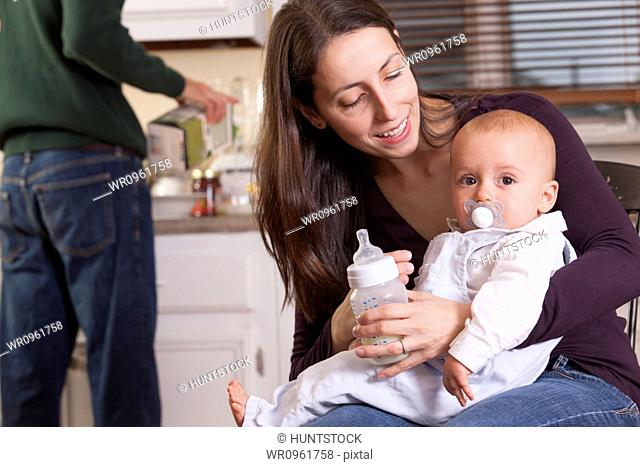Baby in mother's arm with pacifier and father pouring juice