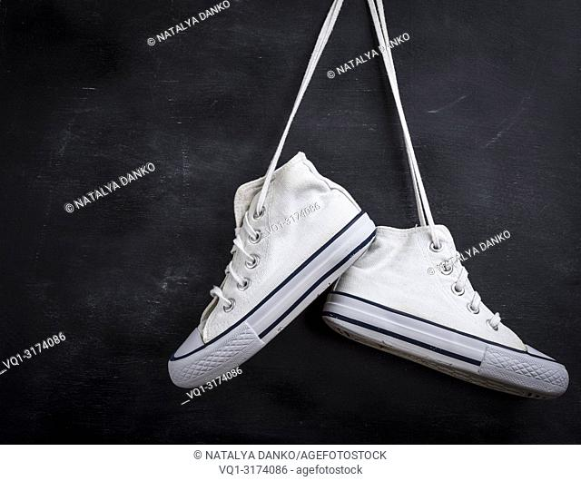 pair of used white textile shoes hang on a black background, close up, copy space