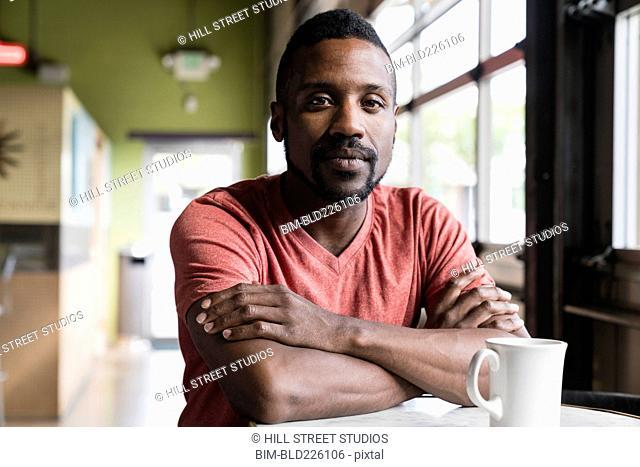 Pensive Black man sitting in coffee shop