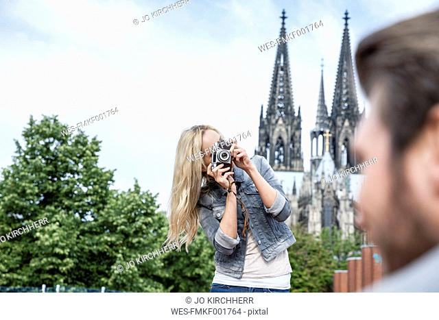 Germany, Cologne, young woman taking a picture of her boyfriend