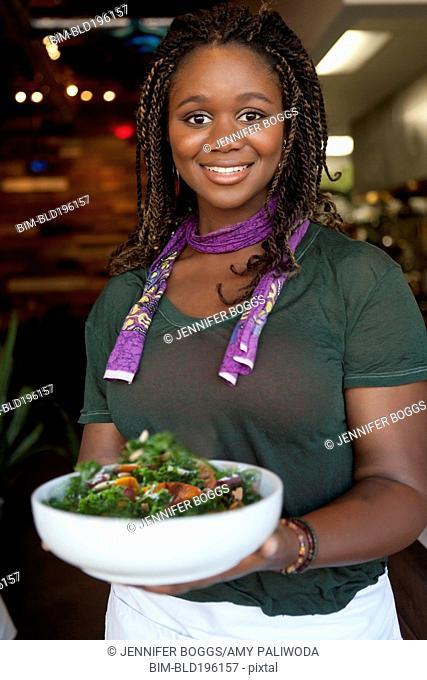 Black waitress serving salad in restaurant