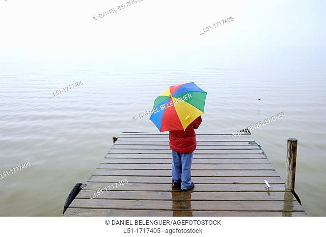 Boy with a multicolored umbrella on a pier in the lake, Albufera de Valencia Nature Reserve , Valencia, Spain