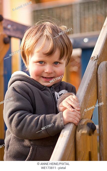 Happy boy three years smiling towards camera, standing on a climbing frame. Verona,Italy