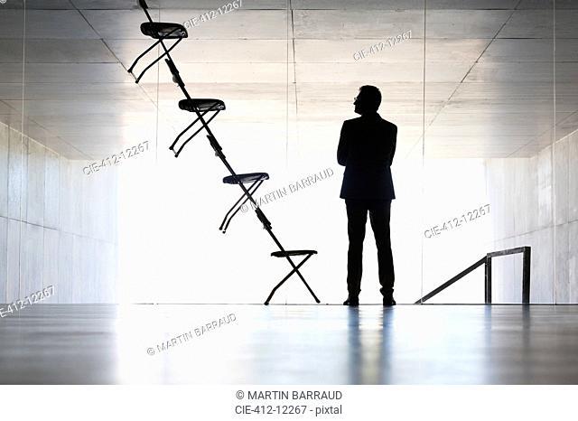Businessman examining office chair installation art
