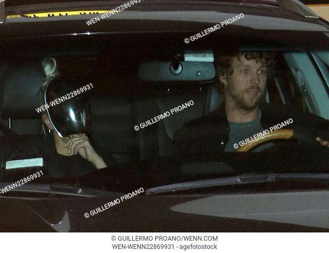 Sia makes every effort to avoid being seen by wearing a metal face mask and then covering her face with her hands as she leaves Katsuya Hollywood with husband...