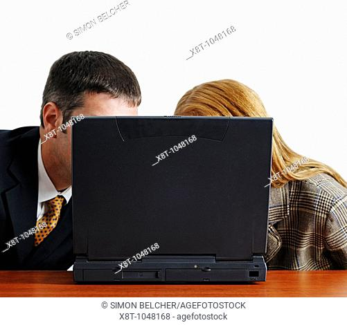 Businessman and Woman Looking at the Monitor of a Laptop in an Office