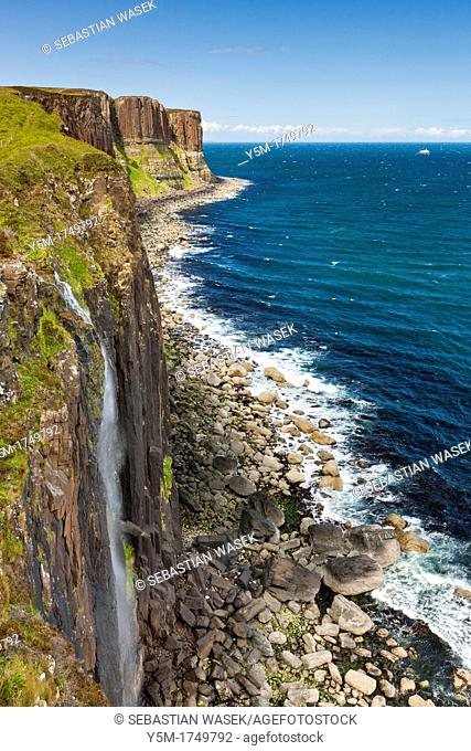 Waterfall flowing over the cliffs of the coast of Isle of Skye, Kilt Rock is in the distance, Trotternish, Scotland, UK, Europe