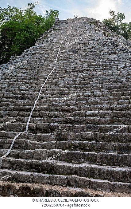 Nohoch Mul, the main pyramid at the Coba Ruins, near Playa del Carmen, Yucatan, Mexico. Climber waving from the top