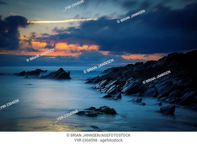 Cloudy sunset over the rocks along the Cornish coast near Newquay, Cornwall, England