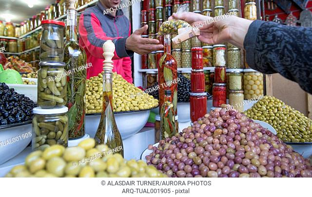 Close-up of hand of customer buying fresh olives at market, Marrakesh, Morocco