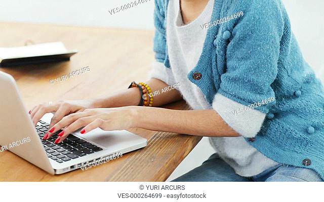 Young creative woman working on her laptop in a bright work space