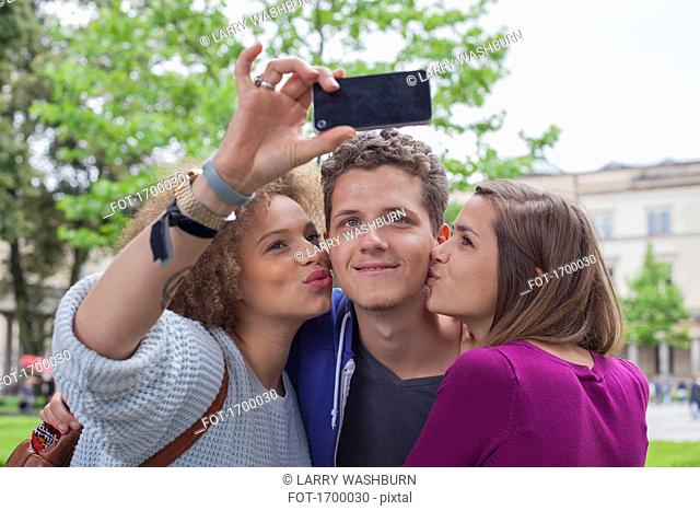 Woman taking selfie with female friend while kissing young male