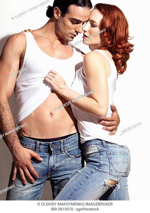 Sexy young couple in blue jeans and white tank tops