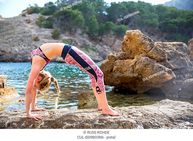 Young woman bending over backwards practicing yoga position on sea rocks, Majorca, Spain