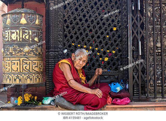 Old woman with prayer beads, Buddhist nun sitting next to a prayer wheel, Boudha Stupa, Kathmandu, Nepal