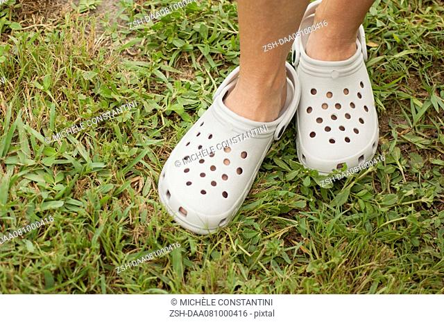 Woman wearing plastic gardening clogs, cropped