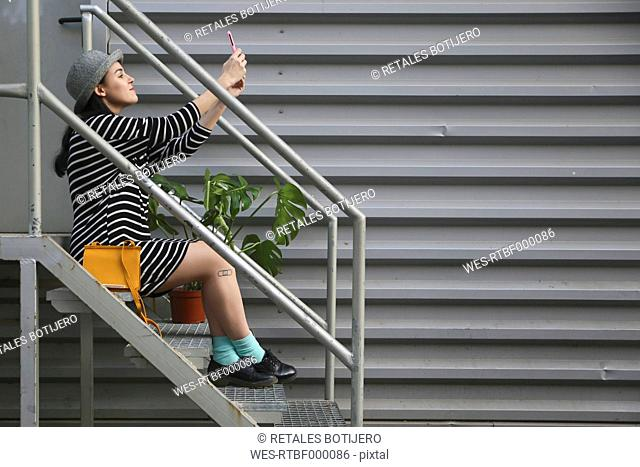 Young woman sitting onb stairs taking a selfie with smartphone