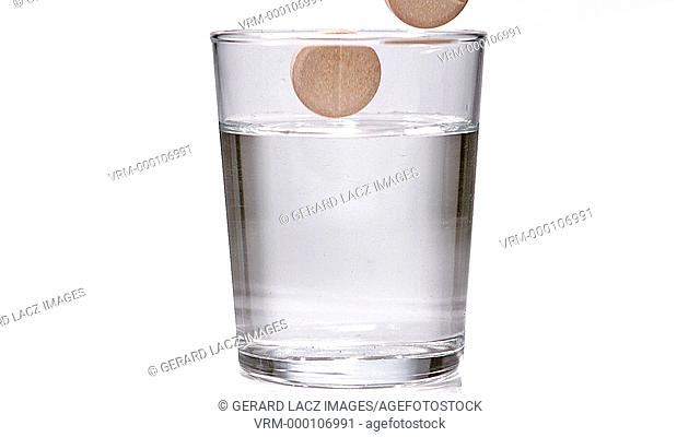 Tablets Falling and Dissolving in a Glass of Water against White Background, Slow Motion