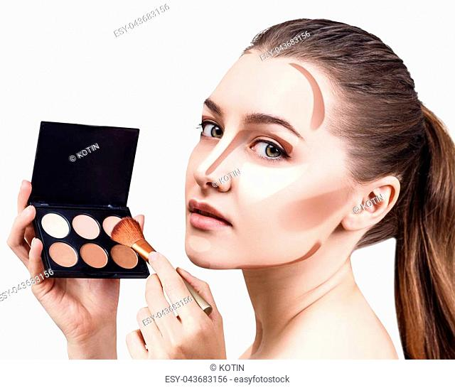 Young woman with contouring make-up holding palette for contouring face. Isolated on white background