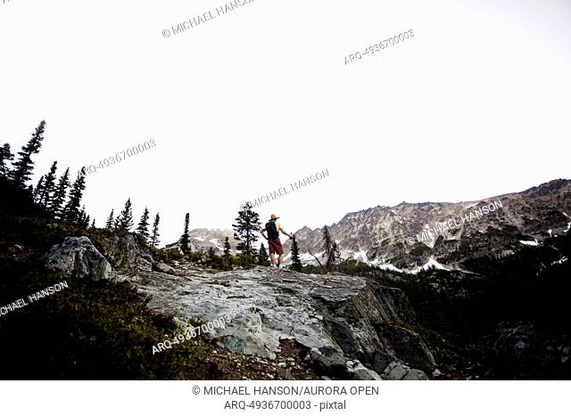 A male hiker on a trail as he attempts to summit a peak on a cloudy day in the North Cascades, WA