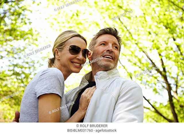 Caucasian couple hugging in park