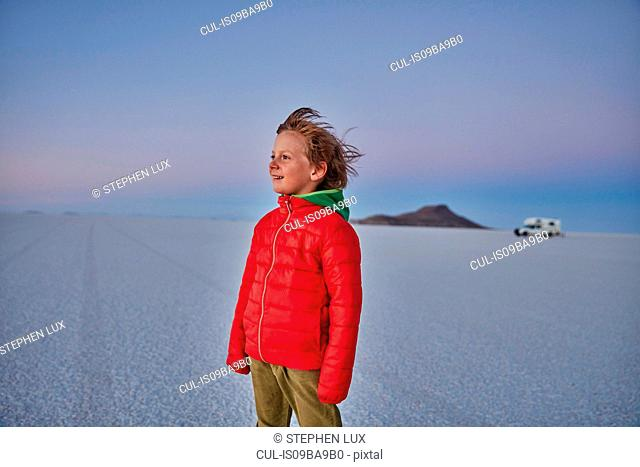 Young boy standing on salt flats, looking at view, recreational vehicle in background, Salar de Uyuni, Uyuni, Oruro, Bolivia, South America