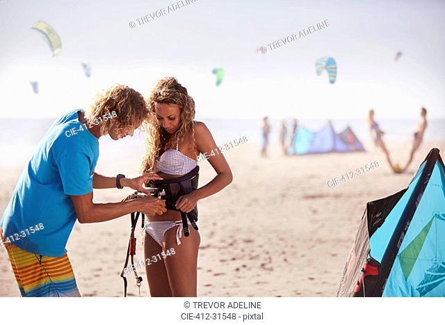 Man fastening kiteboarding safety harness onto woman on sunny beach