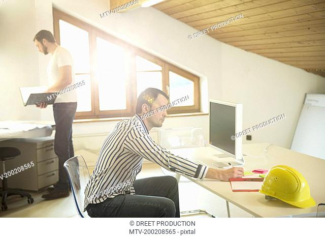 Architect doing paperwork and working on computer in office, Bavaria, Germany