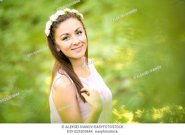 Portrait of a young beautiful girl on a blurred background of green foliage