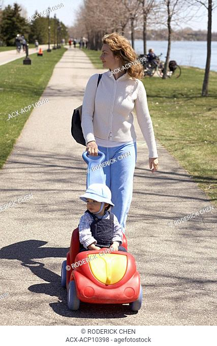 17 months old baby boy in Park Rene Levesque with a toy car with his 35 year old mother, Lachine, Quebec, Canada