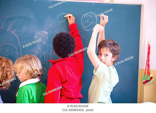 Primary schoolboys drawing on classroom blackboard