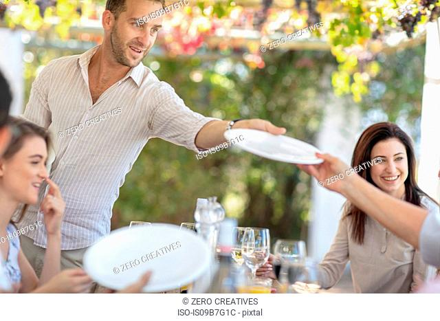 Man passing plate at outdoor family lunch