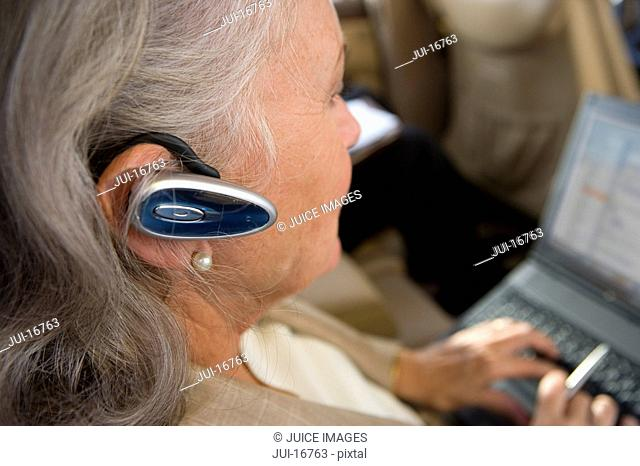 Businesswoman using hands-free device