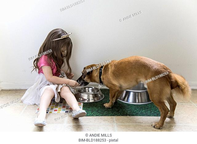 Caucasian girl feeding dog on floor