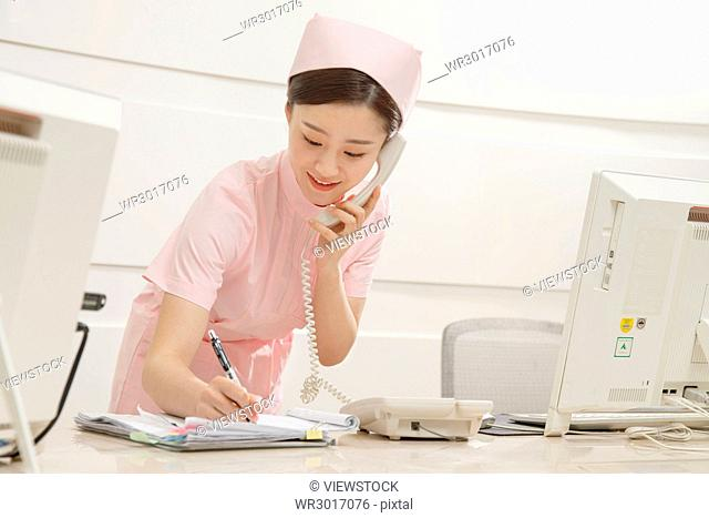 The young woman nurse is on the phone