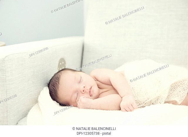 Newborn baby girl asleep on rocking chair with hand nestled up near face; Toronto, Ontario, Canada