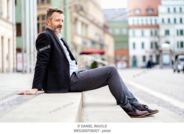 Germany, Zwickau, relaxed mature businessman sitting on steps outdoors