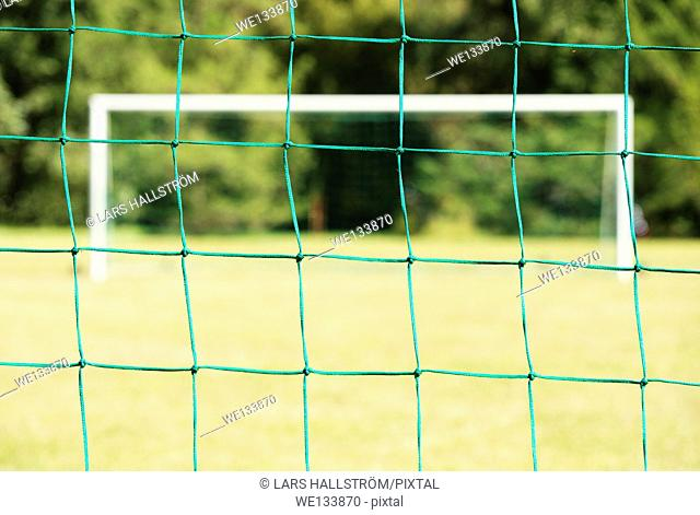 Empty football (soccer) field viewed through the net of the goal