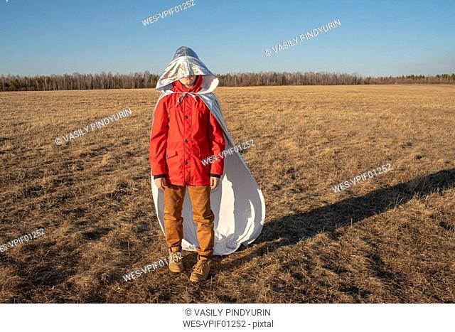 Hood of superhero costume covering boy's face in steppe landscape