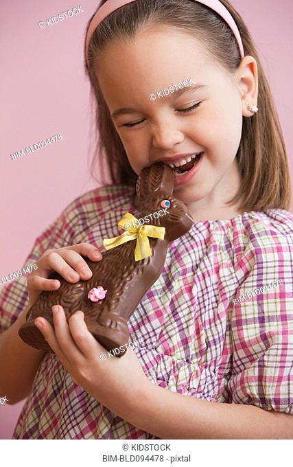 Caucasian girl eating chocolate Easter bunny