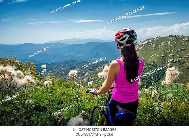 Woman with mountain bike watching a valley below, Canton Wallis, Switzerland