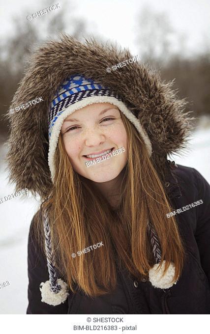 Caucasian teenage girl wearing fur coat and hat in snow
