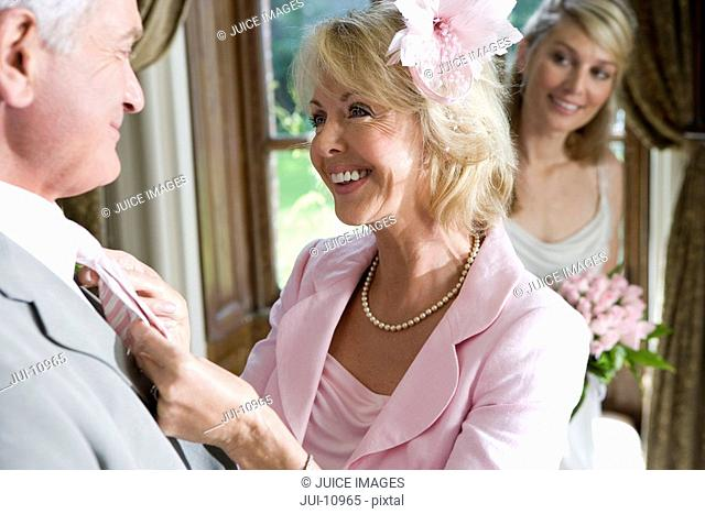 Mature woman adjusting husband's tie, bride in background, smiling, close-up