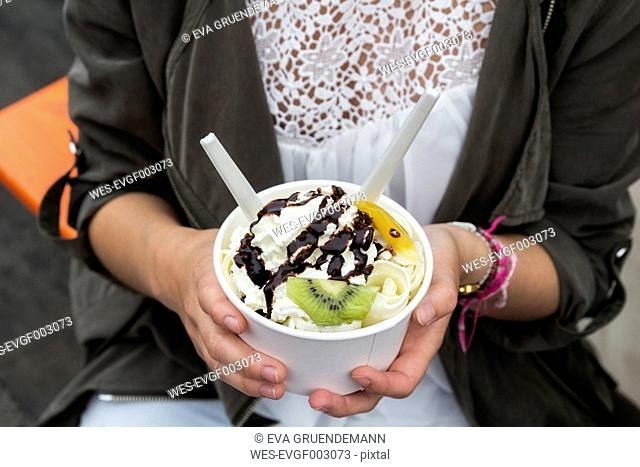 Hands of teenage girl holding cup of Rolled Ice Cream with fruits