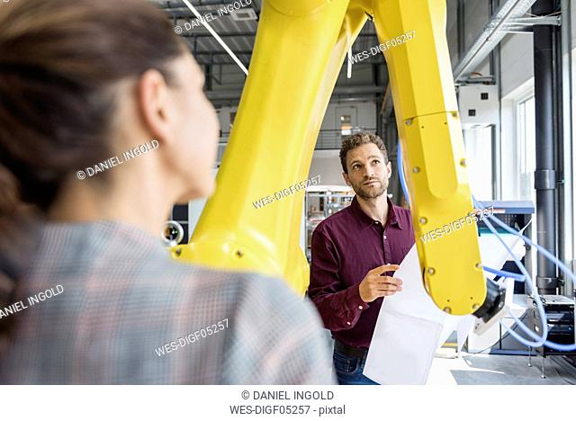 Businessman and woman having a meeting in front of industrial robots in a high tech company